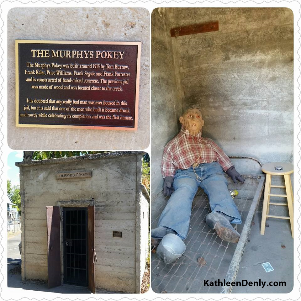 Photograph of The Murphys Pokey by Kathleen Denly. Show the cement exterior with metal doors, a historical plaque, and a sign bearing its name. Also show interior with homemade mannequin sitting on a bare wire cot.